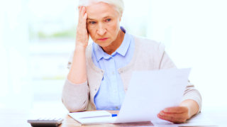 senior woman with papers or bills and calculator