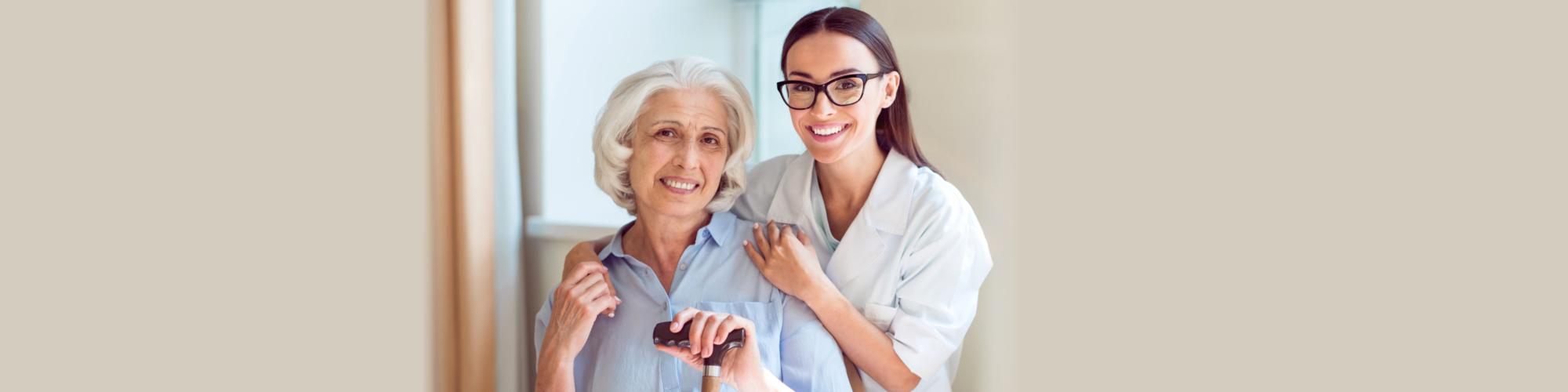 senior woman and a caregiver smiling