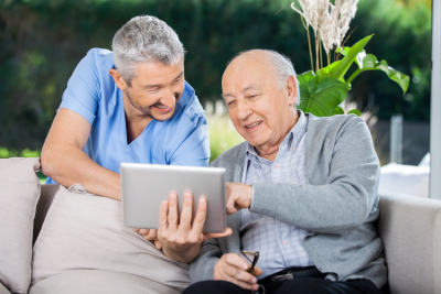 male caregiver and senior man smiling while using tablet computer