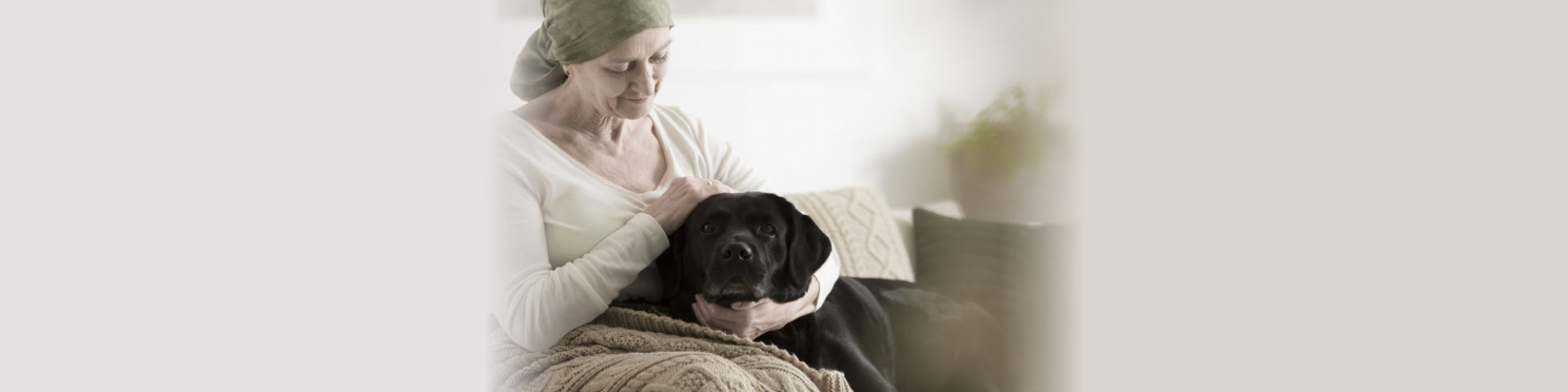 Sick grandmother with headscarf stroking dog while sitting on sofa